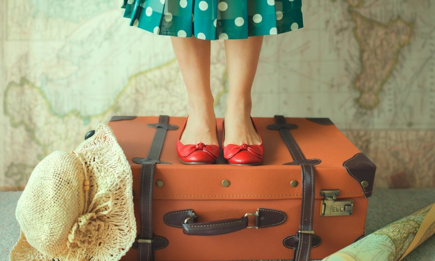 woman in polka dot dress standing on suitcase with map in background 880x528